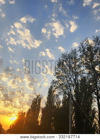 poster of Sunset cloudy sky with picturesque clouds lit by warm sunset sunlight, colorful sunset sky with dramatic sky clouds lit by evening sunlight. Country road at sunset