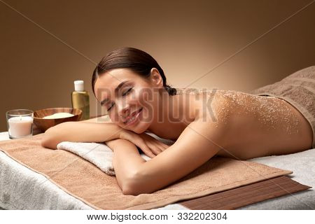 wellness, beauty and relaxation concept - beautiful young woman lying with exfoliating sea salt scrub on skin of her back at spa