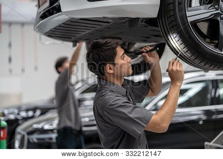 Asian Mechanic Checking And Torch Tire In Maintainance Service Center Which Is A Part Of Showroom, T