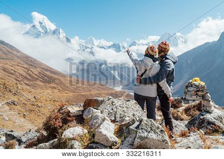 Couple Having A Rest On Everest Base Camp Trekking Route Near Dughla 4620m. Backpackers Left Backpac