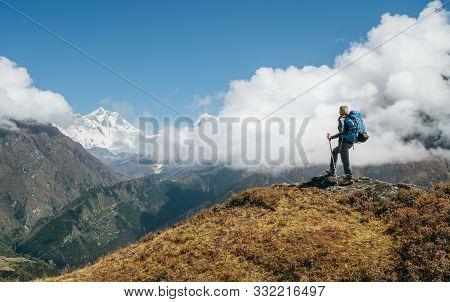 Young Hiker Backpacker Man Using Trekking Poles Enjoying The Nuptse 7861m Mountain During High Altit
