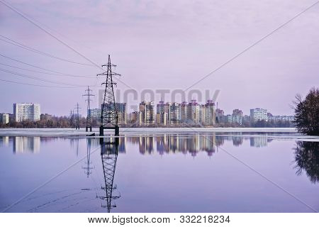 High-voltage Power Line Over The Wide Lake And City In The Distance. Sunset And Reflection In Water.