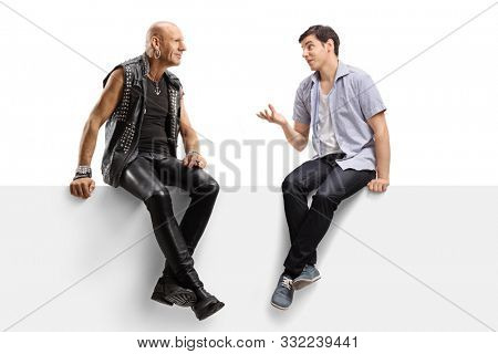 Full length shot of a young man talking to a punk in leather clotes and sitting on a panel isolated on white background