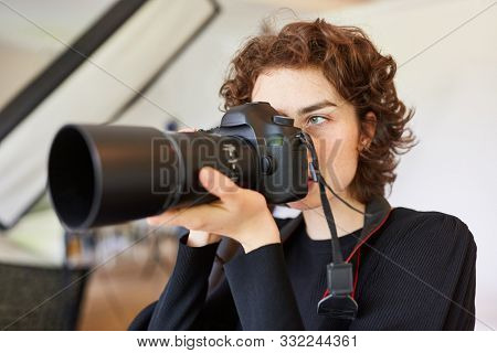 Young photographer or photo-student photographed with digital camera