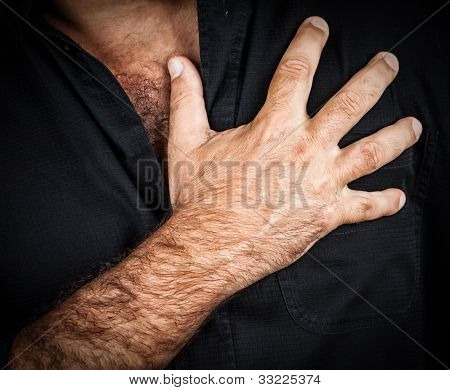 Close up of a hand grabbing a chest on a black background, useful to represent a heart attack or any sentimental concept