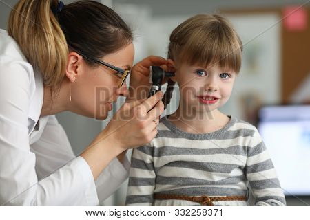 Portrait Of Child Sitting In Modern Hospital Office Of Professional Practitioner Looking Into Ear Wi