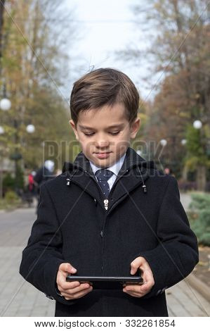 A Schoolboy Enthusiastically Clicks On The Screen Of His Smartphone, Holding It In Both Hands In A H