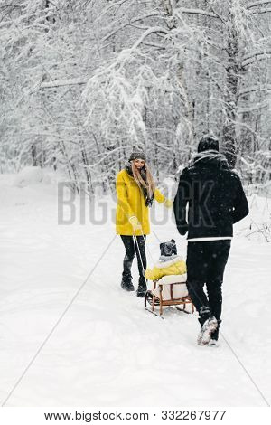 A Beautiful Family Walks Through The Winter Snowy Forest. Mother, Father And Son In Yellow Jackets E