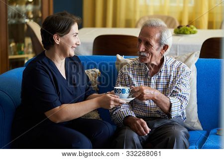 Professional Helpful Caregiver And A Senior Man During Home Visit