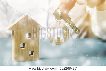 Trinket With Miniature Home In The Hands Of A Businessman And A Wooden House With Snow. Christmas Sa