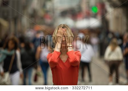 Panic attack in public place.  Woman covers his eyes with his hands surrounded by people walking in crowded street.