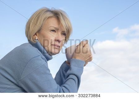 Portrait Of A Pensive Thoughtful Happy Elderly Adult Woman With A Hot Drink, Tea Or Coffee. Senior M