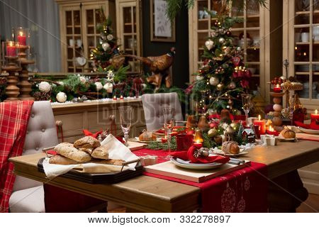 Christmas, holidays and eating concept - table served for festive dinner at home. Living room decorated with lights and Christmas tree. Holiday setting