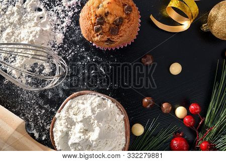 Background With Elaboration Of Muffins For The Christmas Holidays On Black Table With Ingredients An