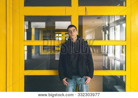 Portrait Of A Casual Young Man In Front Of Yellow Windows