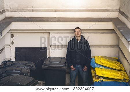 Portrait Of A Casual Young Man Standing Between Garbage Cans