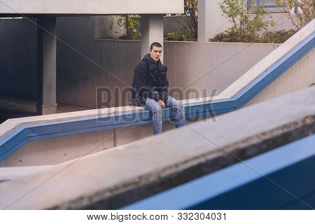Portrait Of A Casual Young Man In Sitting On A Concrete Wall
