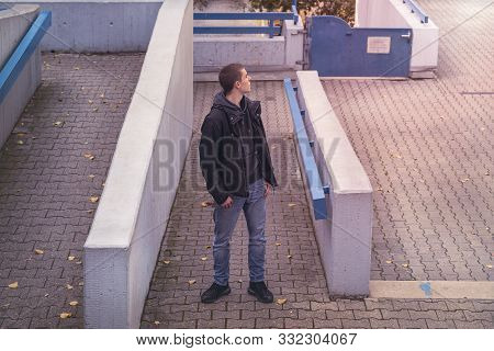 Young Man Looking Around Between Concrete Walls