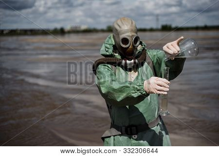 A Male Environmentalist In A Green Protective Suit And Gas Mask Takes A Sample Of Water In A Pollute