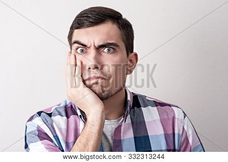 Portrait Of European Man With Puzzled Face Holding His Hand To His Cheek, Bewilderment, Toothache