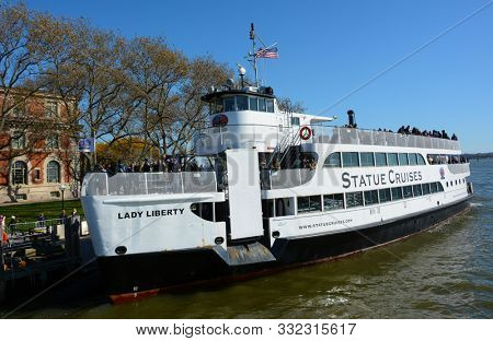 ELLIS ISLAND, NEW YORK - 04 NOV 2019: Lady Liberty at dock at Ellis Island, a ferry service that provides the tourist transportation to The Statue of Liberty and The National Museum of Immigration