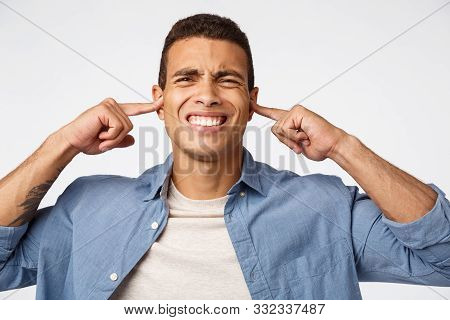 Disappointed Upset Man In Blue Shirt Over T-shirt, Grimacing From Discomfort And Dislike, Cover Ears