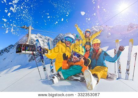 Happy family enjoying ski winter vacations in mountains. Playing with snow, Sun in high mountains. Winter holidays.