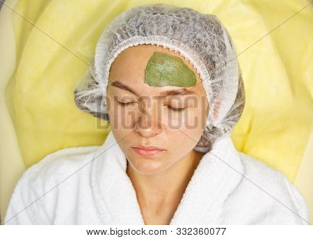 The concept of cosmetology. Close-up of a beautician applying a green mask with a brush on a woman's face poster