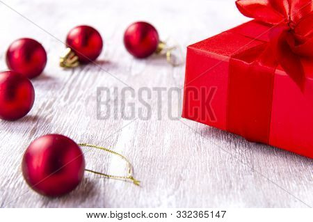 Christmas Composition. Red Gift Box With Red Ribbon On A Wooden Background With Red Balls. View From
