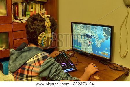 Turin, Piemonte, Italy. November 2019. A Caucasian Boy Is Playing Computer Games. Use A Gaming Keybo