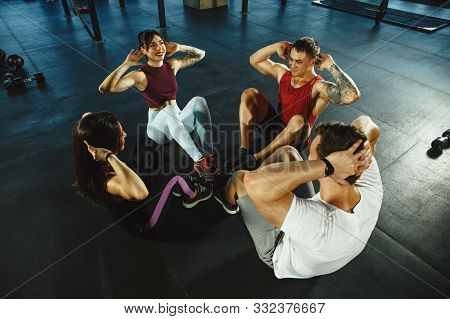A Group Of Muscular Athletes Doing Workout At The Gym. Gymnastics, Training, Fitness Workout Flexibi