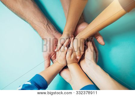 Closeup Of The United Hands Of One Family On A Blue Background. Dad, Mom, Kids Holding Hands. Large