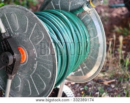 Green Gardening Hose For Watering Flowers And Grass Wrapped Around The Aluminum Carrier. Garden Wate