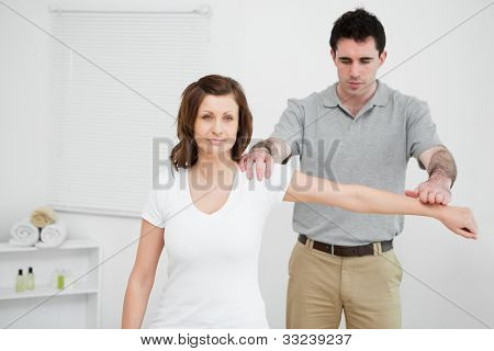 Serious osteopath pressing down the arm of a patient in a medical room