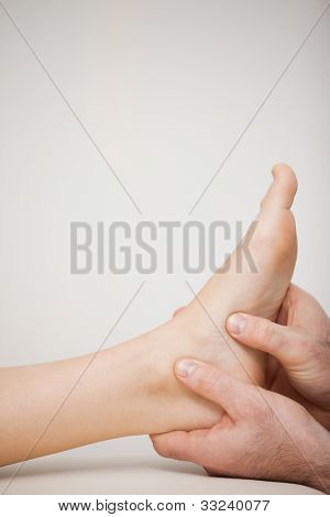 Two thumbs being placed on the side of a foot in a medical room poster