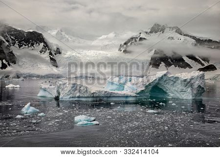 Iceberg and icy waters with glacier backdrop along the Antarctica Peninsula.