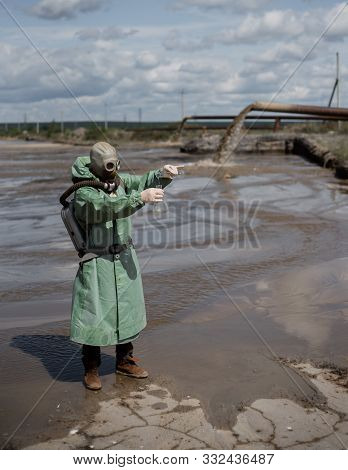 A Male Environmentalist In A Green Protective Suit And Gas Mask Takes A Sample Of Water. The Scienti