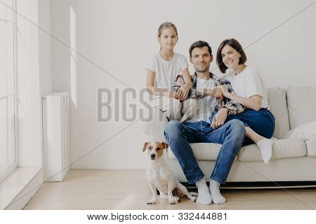 Horizontal Shot Of Affectionate Family Pose Together On Couch In Empty Spacious Room With White Wall