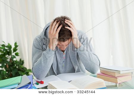 Distressed student in front of his books while holding his head