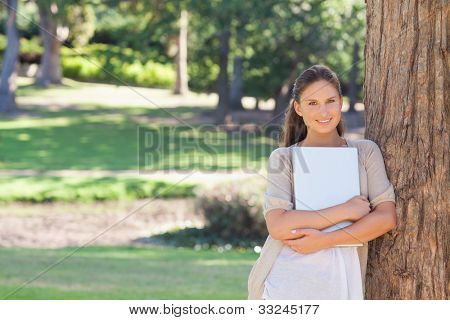 Smiling young woman with a laptop leaning against a tree