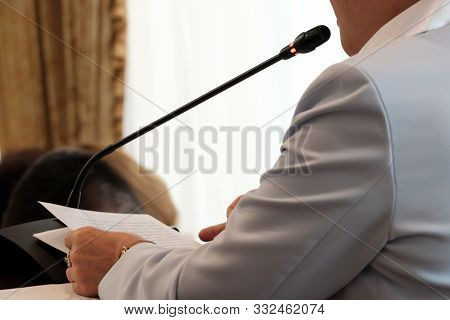 Oratory Of An Abstract Woman In Front Of A Microphone. Report Meeting, Discussion, Government Speech