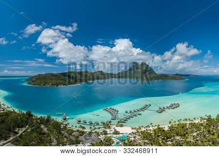 Panoramic Aerial View Of Luxury Overwater Villas With Palm Trees, Blue Lagoon, White Sandy Beach And