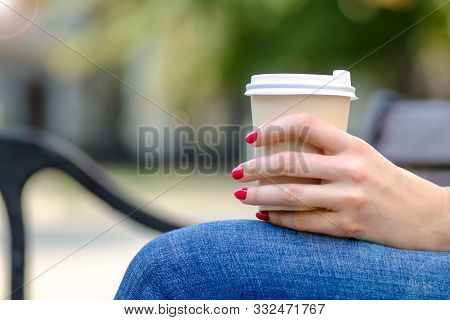 Girl In Hand With Manicure Holds Aromatic Tasty Coffee In A Disposable Cup On A Bench On A Sunny Day