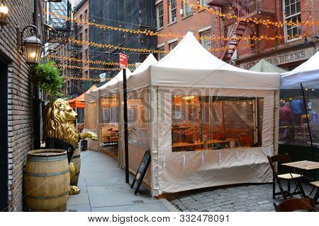 NEW YORK, NY - 05 NOV 2019: Stone Street Restaurants set up tents in the a narrow cobblestone street in the heart of the Financial District.