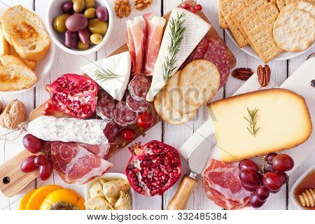 Charcuterie Board Of Assorted Cheeses, Meats And Appetizers. Top View Table Scene On A White Wood Ba
