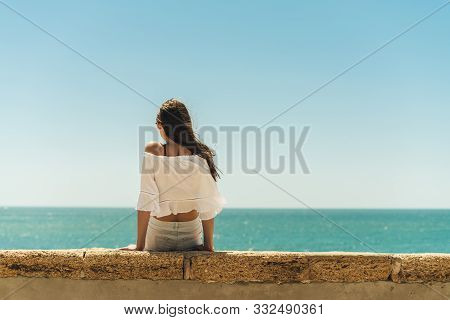 Brunette Sitting On The Parapet With Her Back To The Camera On The Background Of The Ocean, Legs Dan