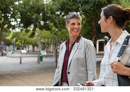 Successful entrepreneur and her colleague in a conversation outdoor. Mature businesswoman and her partner walking on street while chatting. Two formal women manager and accountant going to work.