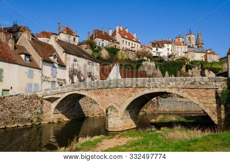 Stone Bridge Over The River In The Old French Town. On The Mountain There Are Traditional Houses Wit