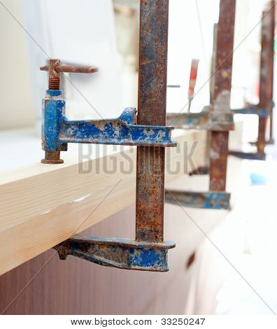 Carpenter screw clamp tools pressing wood slats and white glue
