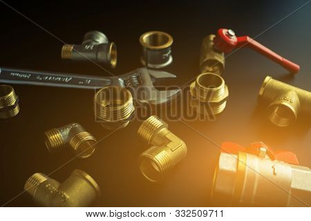 Plumbing Equipment On A Black Background. Valves And Wrench.